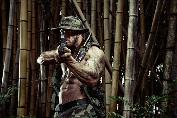 Fighting his way through the jungle the soldier raises his rifle to fire on the enemy.