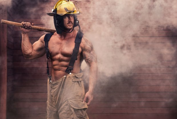 The fireman walks away from the smoldering embers of the fire.